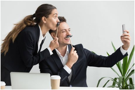 man and woman in black business suits posing for fun selfies with moustaches on sticks